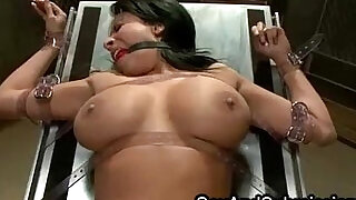 7:00: Busty gaged babe is fucked while standing and flogged while lying